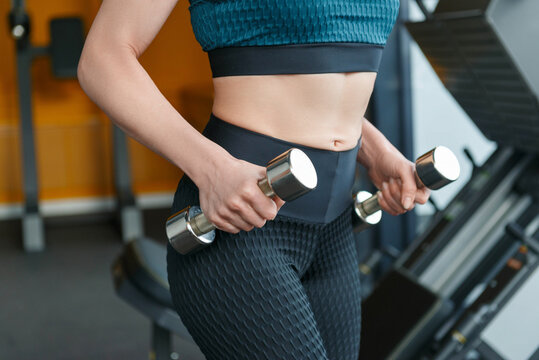 Workout in gym by a beautiful woman, woman is using dumbbell.