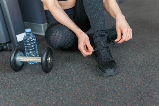 Active lifestyle and fitness concept womans hands tying shoelaces on sport sneakers in gym.