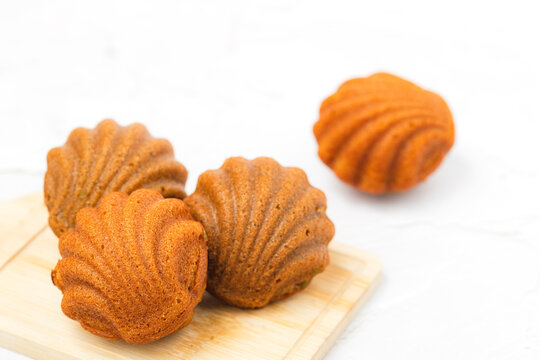 Madeleine cakes with a distinctive shell-like shape on white background for bakery, food and eating concept