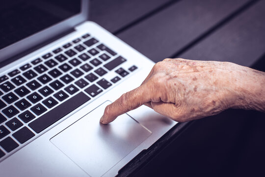 old persons finger on laptop keyboard