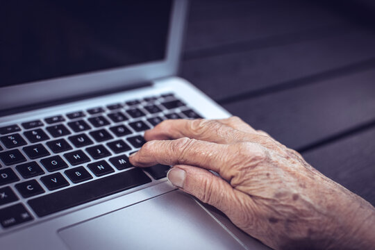 old persons hand on computer keyboard
