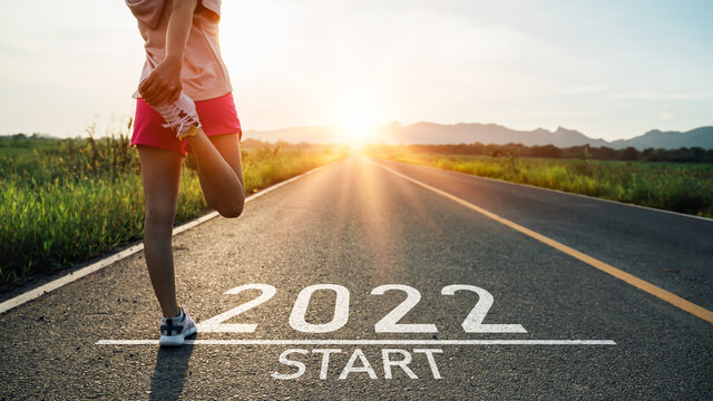 New year 2022 or start straight concept.word 2022 written on the asphalt road and athlete woman runner stretching leg preparing for new year at sunset.Concept of challenge or career path and change.