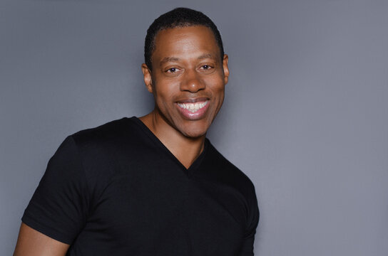 Portrait of  smiling African American man in plain black t-shirt standing in front of gray background