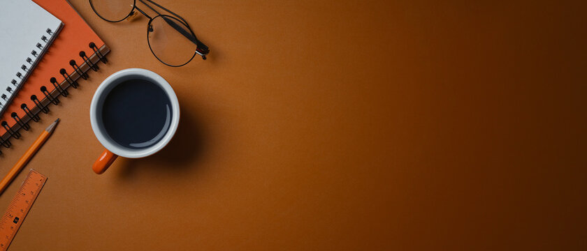 A coffee cup, glasses and notebook on orange leather with cop space.