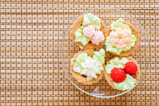 Delicious sweet sandbreaking baskets with cream in a glass plate on a bamboo mat.