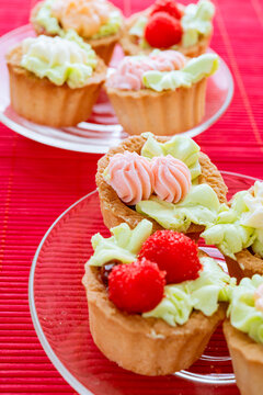 Tasty sweet sandbag baskets with cream on a glass saucer on a red background.
