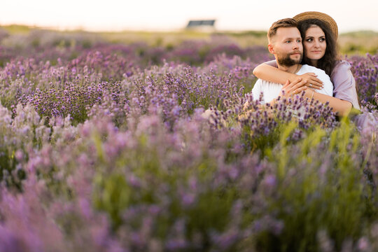 Adorable beautiful couple sitting in the lavender field, hugging, enjoying moments together, having a romantic date. Pretty woman cuddling handsome man, spending weekends outdoors concept