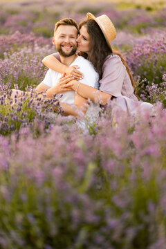 Happy young couple having a romantic date at the lavender field, sitting and hugging, spending weekends outdoors. Attractive woman gently kissing charming man, enjoying moments together