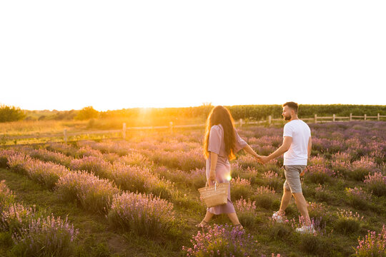 Stylish young adult couple walking at lavender field, having a romantic date. Handsome man hold a hand of beautiful woman, enjoy moments together, meeting the sunset, spend weekends outdoors concept