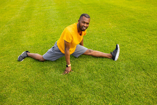 Smiling african american male in stylish sportswear sitting at the grass, trying to do a split, stretching legs. Athletic man is working out, doing warm up before training outdoors concept