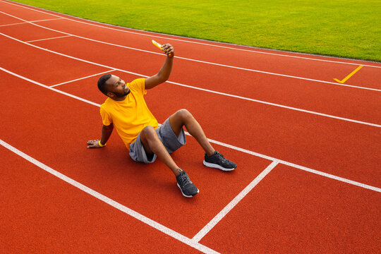African american sportive man in yellow t-shirt sitting at the stadium track, using smartphone to take a selfie, smiling. Happy male trainer is sitting at the stadium, take a break from workout