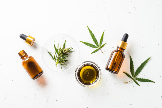 CBD oil and cannabis leaves at white table. Medicine and cosmetic product. Flat lay image.