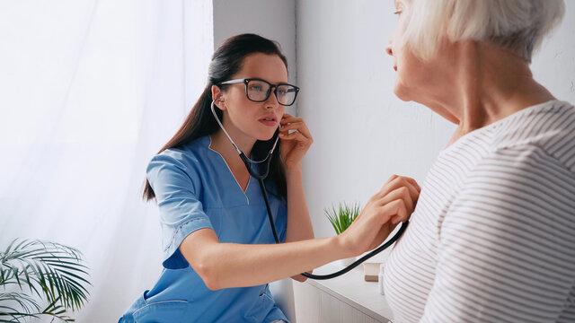 brunette nurse in eyeglasses examining senior woman with stethoscope