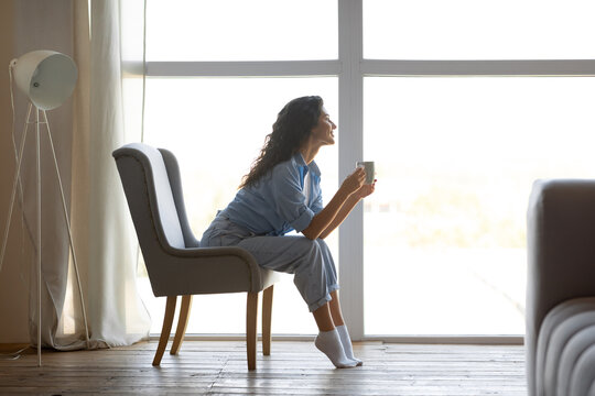 Side view of pretty young woman drinking hot coffee in cozy chair near window indoors, copy space