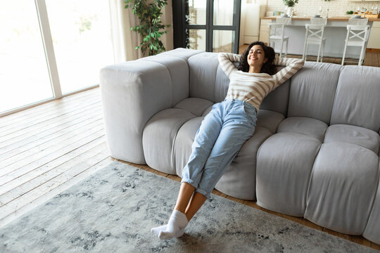 Relaxing weekend morning at home. Happy young woman resting on comfy couch with closed eyes, indoors