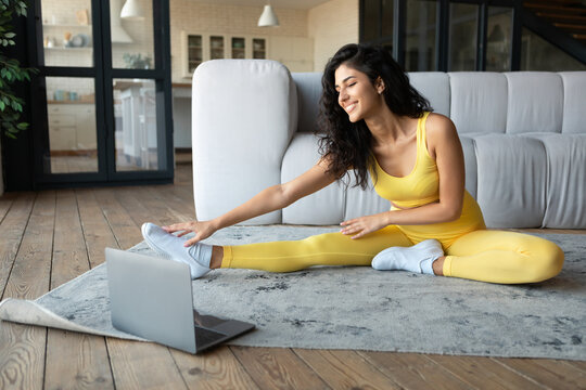 Home workout videos. Fit young woman in sportswear stretching on floor while watching online tutorial via laptop