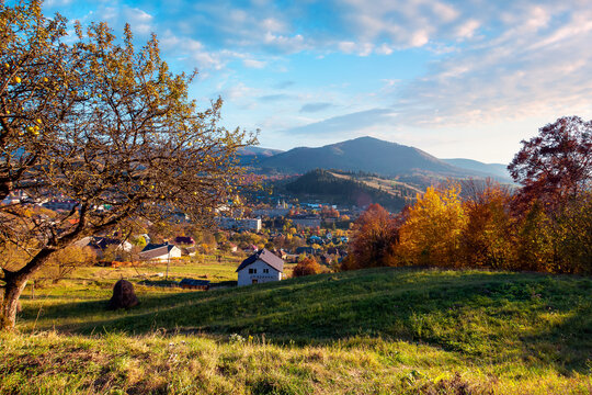 carpathian rural landscape in autumn. village in the valley at the foot of the mountain. beautiful countryside scenery in evening light. trees in fall foliage on the grassy hills