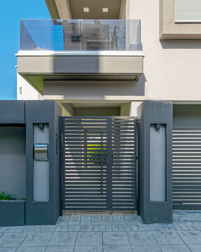 modern house front entrance metallic door by the sidewalk