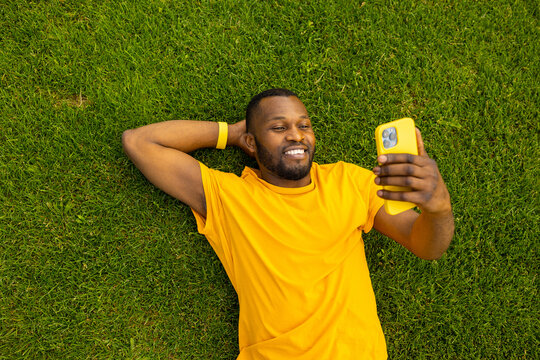 Happy young adult man laying on the grass, using smartphone, browsing internet. Joyful african american male relaxing, taking a break after workout outdoors, having a video call from friends, smiling