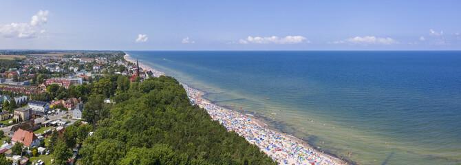 Obraz Morze bałtyckie, w tle miejscowość Sarbinowo i zatłoczona plaża - fototapety do salonu