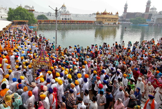 Sikh devotees carry their holy book Guru Granth Sahib in a palanquin during a religious procession, in Amritsar