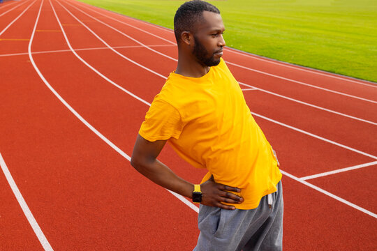 Sportive young adult man standing at stadium track, warming up before running. African american male is working out, stretching back, training outdoors, healthy lifestyle concept