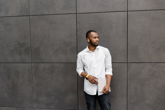 Serious confident young adult businessman is standing outdoors in white shirt, looking at the side. Stylish african american freelancer thinking about new ideas for the project or presentation