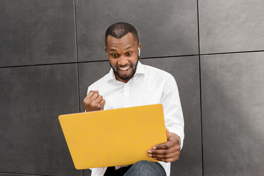 Overjoyed male student or employee using laptop, excited about exam results or work promotion. Happy businessman having video call with colleagues, listen great news about his project, success concept