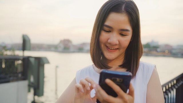 Happy young Asian woman blogger tourist with casual style hold smartphone look with smile joyful with beautiful sunset on river view near cafe in city town. Lifestyle tourist travel holiday concept.