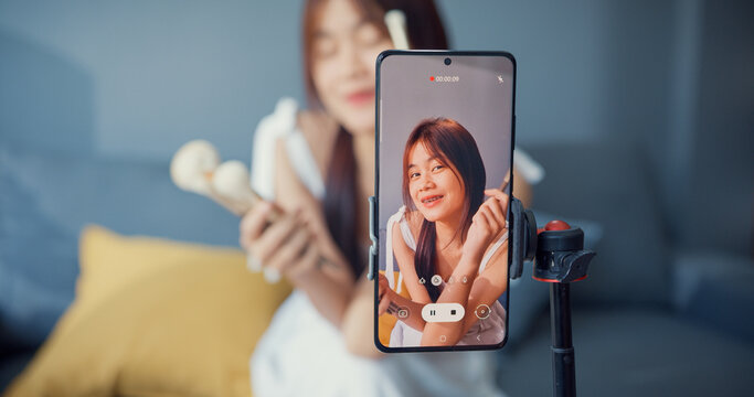Happy young Asian girl makeup vlogger front of phone camera enjoy review talk with audience in living room at house. Social distance coronavirus pandemic concept. Freedom and active lifestyle concept.