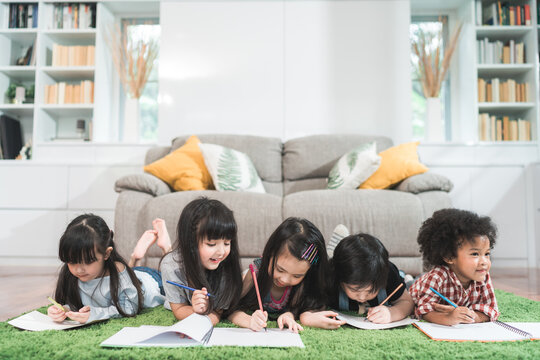 Group of children drawing in classroom, Multi-ethnic young boys and girls happy funny study and play painting on paper at elementary school. Kids drawing and painting at school concept.