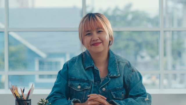 Young Asian creative woman smiling in office. Business female happy relax after work, looking to camera, business situation in modern workplace concept.