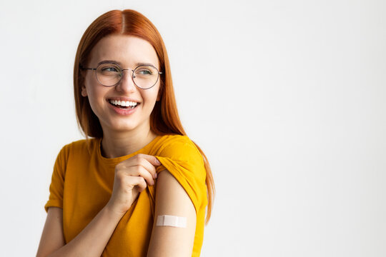 Covid-19 vaccinated caucasian smiling young woman showing arm with plaster