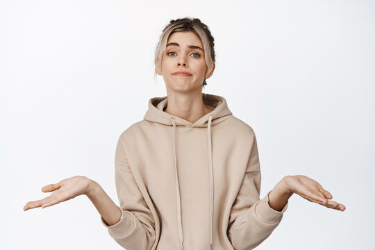 Portrait of blond girl shrugs, shows empty hands, apologizing smile, stands against white background