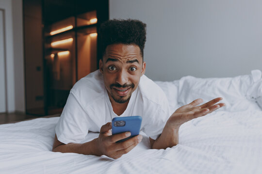 Full length young sad scared african american man in nightwear using mobile cell phone lying in bed rest spend time in bedroom lounge home in own room house wake up dream be lost in reverie good day.