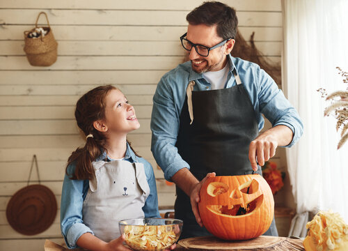 Smiling father showing his little daughter how to carve pumpkin with spooky face for Halloween