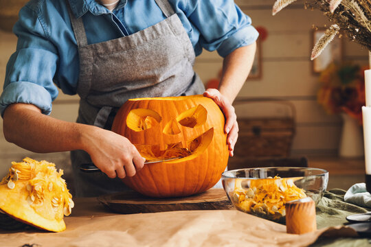 Woman in apron standing in kitchen and carving large orange Halloween pumpkin