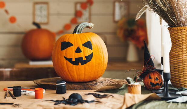 Carved orange pumpkin with drawn spooky face standing on wooden table in cozy rustic kitchen