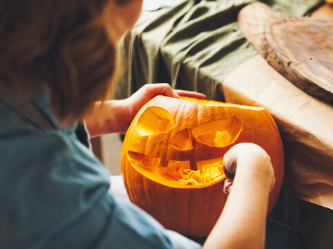 Cropped shot of woman carving large orange pumpkin while preparing for Halloween party