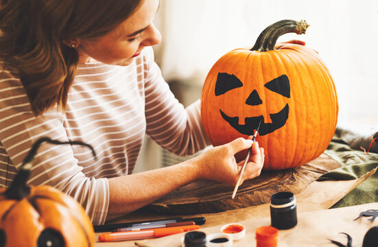 Young woman creating jack-o-lantern while sitting at table in kitchen at home