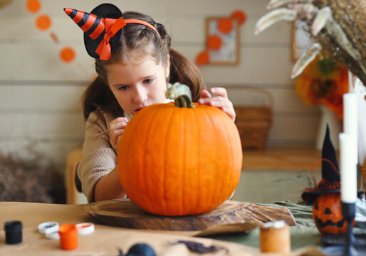 Smiling little kids girl making jack-o-lantern at home, drawing scary face on pumpkin