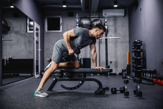 Man doing exercise with dumbbell leaning on sports bench in the gym. Photo of a sexy muscular man in sportswear and good physique on grey background. Strength and motivation, sport, fitness goal