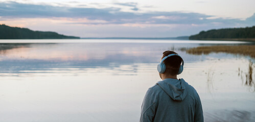 Obraz Balance calmness and harmony with yourself. A man meditates with headphones in nature. He listens to pleasant, calm music. - fototapety do salonu