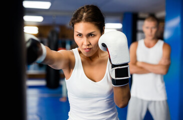 Obraz Asian woman in boxing gloves exercising jabs with punchbag during her boxing training. Her trainer standing behind and observing. - fototapety do salonu