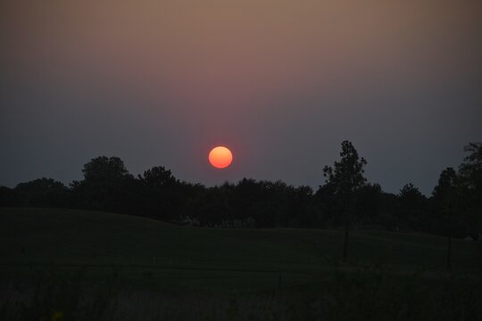 Sunset through wildfire ash. The sun is without sunspots.