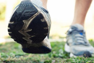 Closeup view of runner's shoes running throug the countryside
