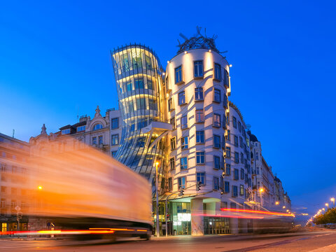 Dancing house in Prague at night with glowing strips of car lights , Czech republic. Travel and sights of city breaks. landmarks, travel guide and postcard