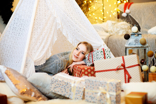 Pretty blonde lady woman girl laying on Christmas giftboxes wear knitted pullover in decorated living room