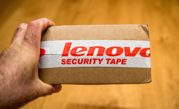 London, United Kingdom - Ap 21, 2021: POV male hand holding cardboard package with FRU object replacement part with Lenovo Inscription and Security tape red text on it