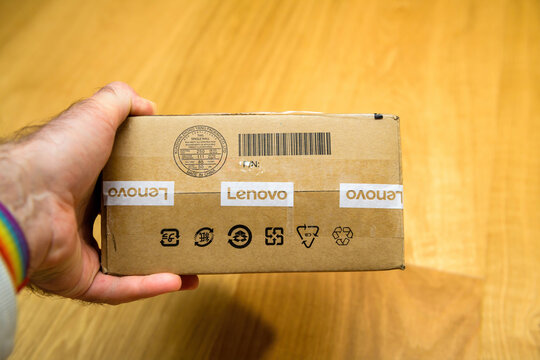 London, United Kingdom - Ap 21, 2021: POV male hand holding cardboard package with FRU object replacement part with Lenovo logotype inscription